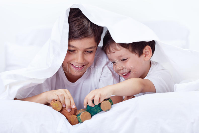 Boys playing in bed with wooden toys royalty free stock image