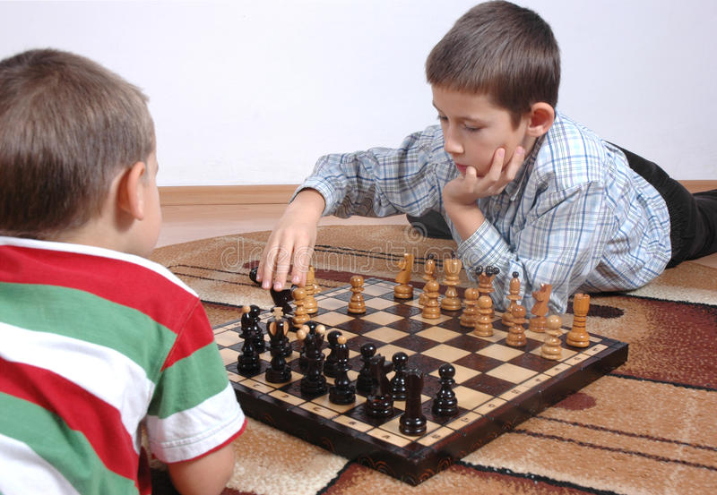 Boys playing chess royalty free stock photo