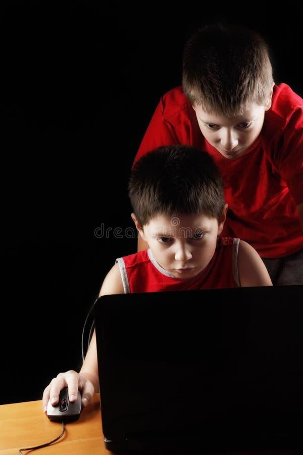 Boys playing computer game stock photography
