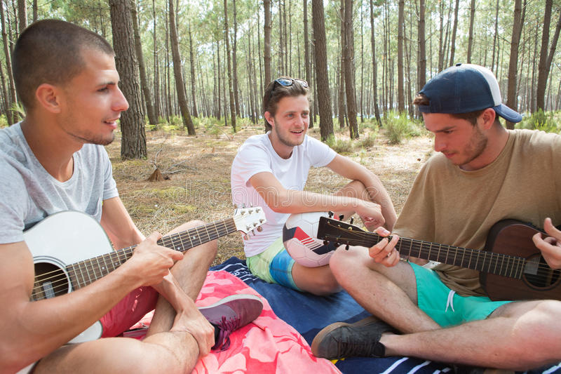 3 boys playing guitar in forest. 3 boys playing guitar in the forest stock photo