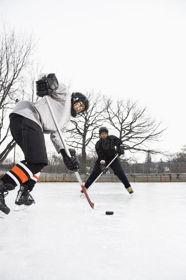 Boys playing ice hockey. royalty free stock images