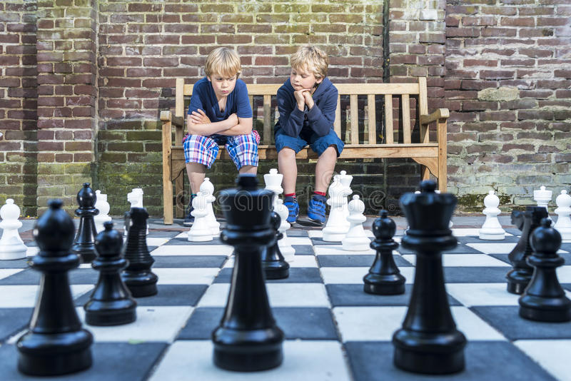 Boys playing outdoor chess royalty free stock photos
