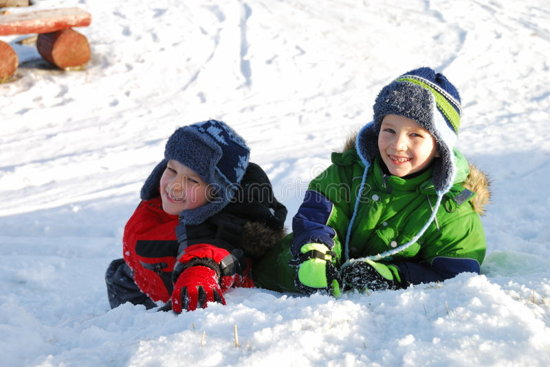 Boys playing in snow. Two children playing together in the snow. They are both boys and are having fun royalty free stock photography