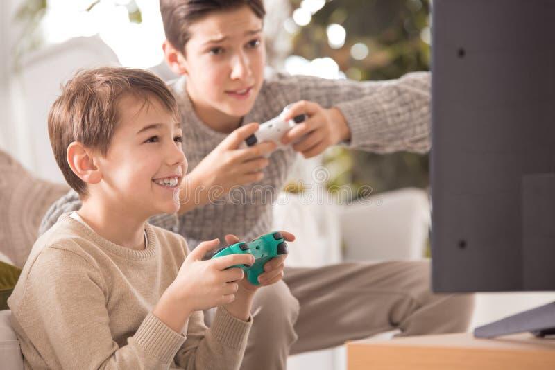 Boys playing videogame stock photography