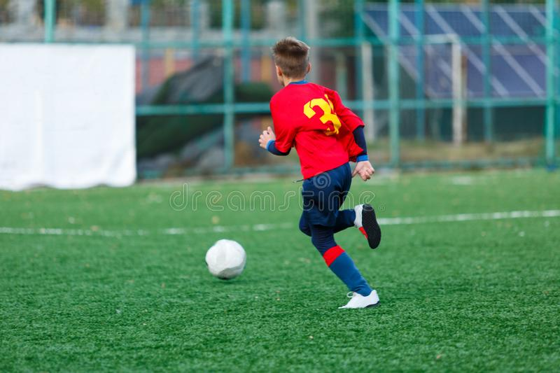 Boys in red and blue sportswear plays  football on field, dribbles ball. Young soccer players with ball on green grass. Training, football, active lifestyle royalty free stock images