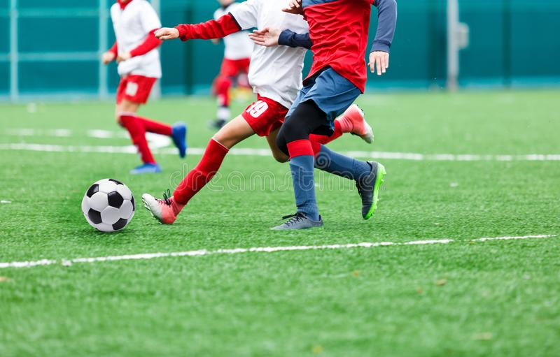 Boys in red and white sportswear plays soccer on green grass field. Youth football game. Children sport competition. Kids plays outdoor, activities, training royalty free stock photos