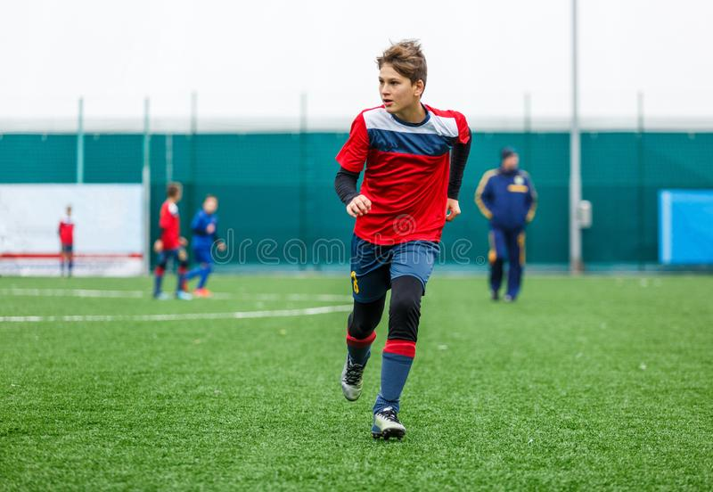 Boys in red white sportswear running on soccer field. Young footballers dribble and kick football ball in game. Training royalty free stock photo