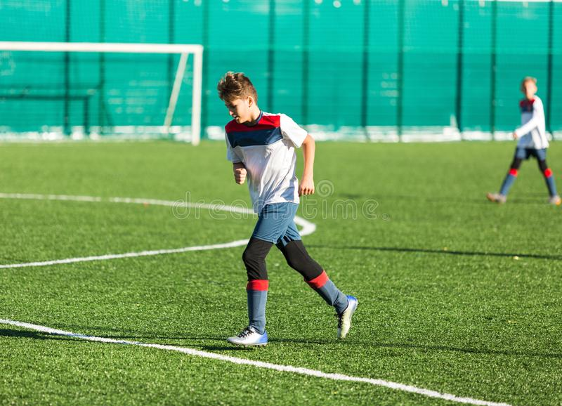Boys in red white sportswear running on soccer field. Young footballers dribble and kick football ball in game. Training, stock photo