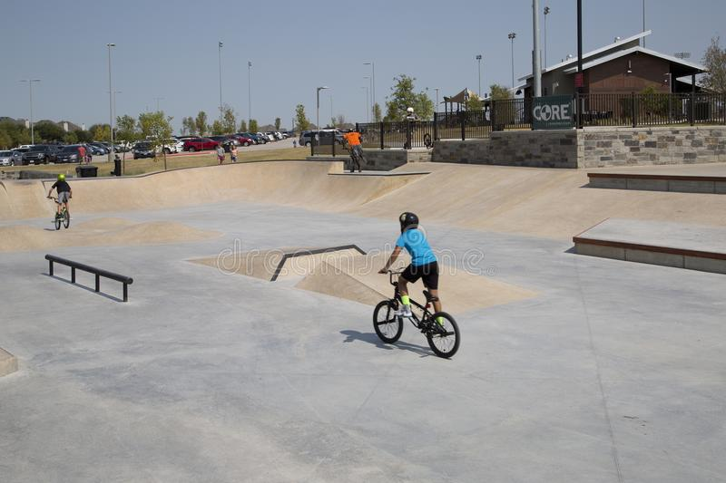Boys ride bike at Skate Park Frisco Texas. Boys ride bicycle , it is Skate Park at Northeast Community Park, city Frisco Texas USA stock photography