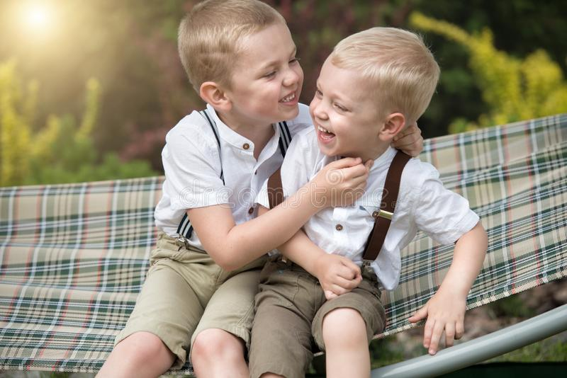 The two brothers rest,telling secrets in his ear.Boys ride in the hammock. royalty free stock photography