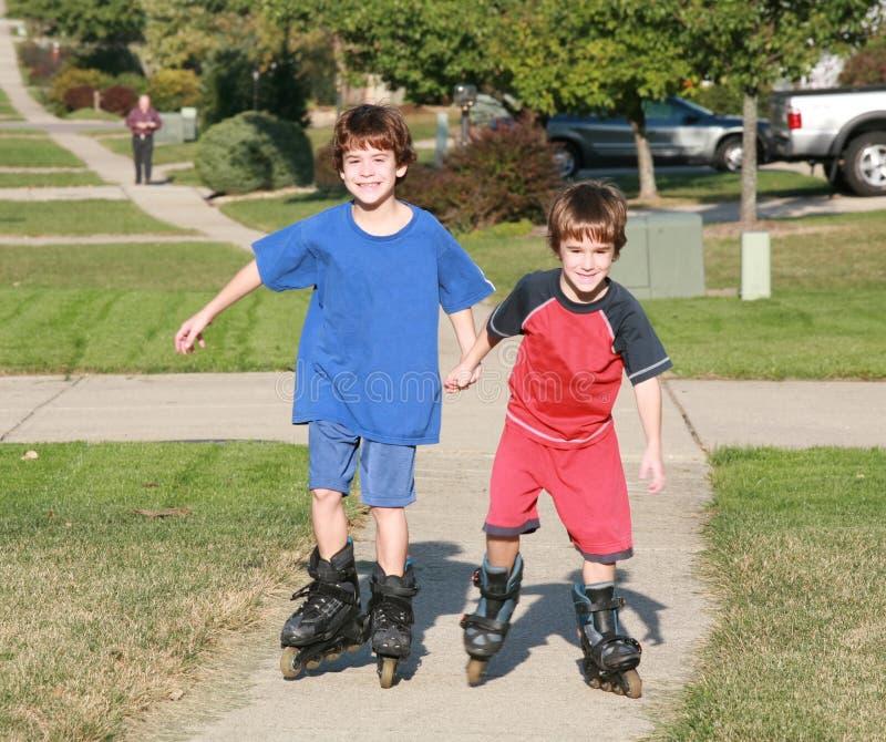 Boys Rollerblading. Two Boys Roller Blading Up a Neighborhood Sidewalk royalty free stock image