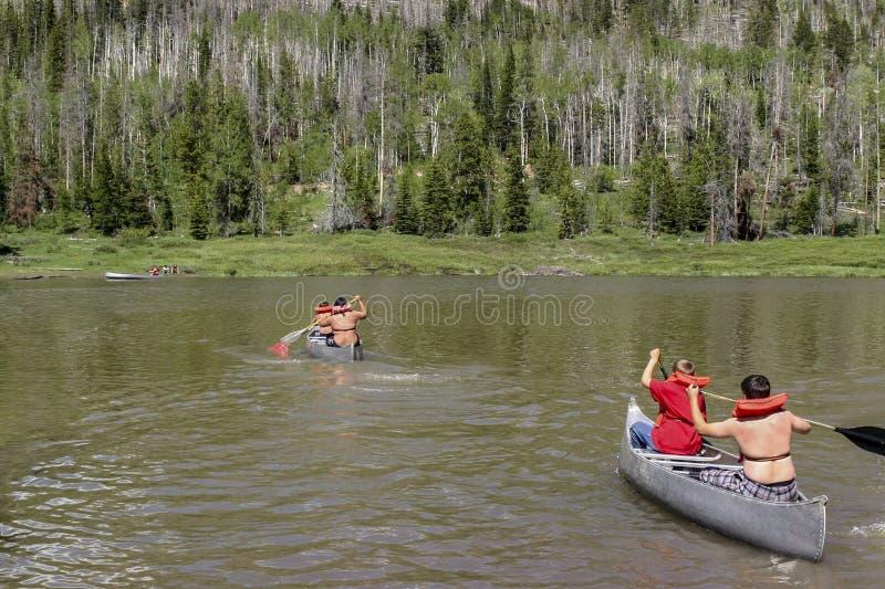 Boys row canoes across a lake royalty free stock photography