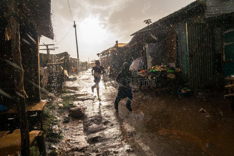 Boys running through african market during rain royalty free stock photos