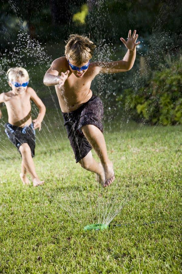 Download Boys Running Fast Through Lawn Sprinkler Royalty Free Stock Photos - Image: 16753778