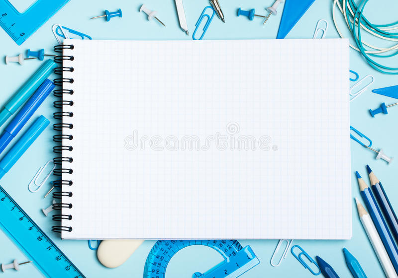 Boys` school supplies. School supplies of blue and white colors on a blue background and notebook. Male or boyish still life on the topic of school, study royalty free stock photo
