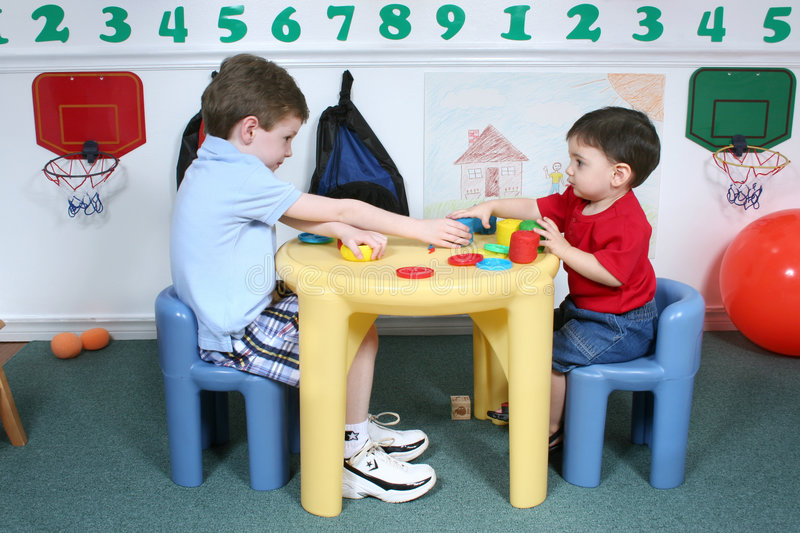 Boys Sharing Colorful Doah at Preschool. Four year old and two year old boy playing with colorful doah at preschool. Image on wall not copyrighted. Shot with the royalty free stock image