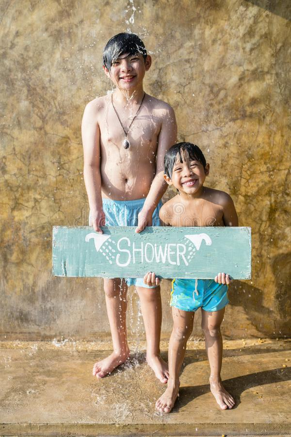 Boys showering at a swimming pool stock images