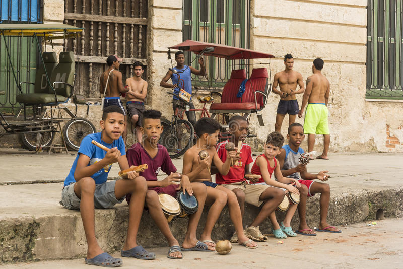 Boys on sidewalk playing percussion instruments Havana. Boys sitting on sidewalk plying different percussion instruments to get some money. Old Havana, Cuba stock images