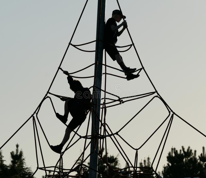 Boys in silhouette on rope and pole adventure climbing frame. stock image