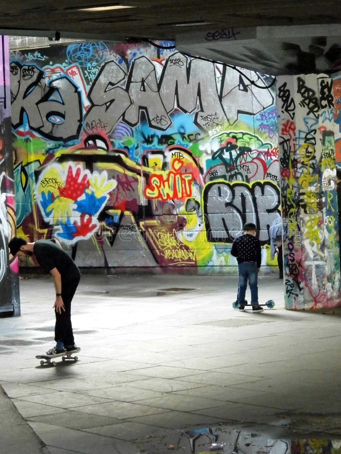 Boys at skateboard park. Southbank, London: Boys at skateboard park, showing graffiti. This is still under threat of moving upstream stock photo