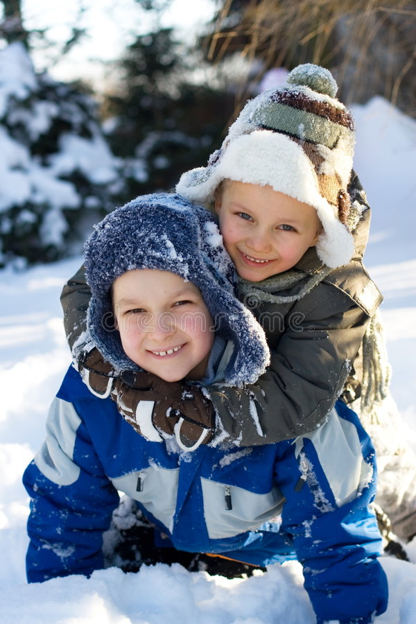 Boys On Snow. Two young brothers embracing while playing in snow