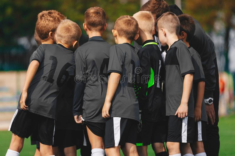 Boys Soccer Team in Huddle. Kids Sport Football Team Gathering with Coach on Sports Venue. Grass Soccer Stadium in the Background royalty free stock images