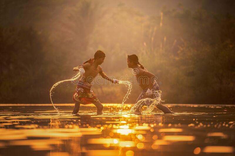 Boys splashing in water at dawn royalty free stock image