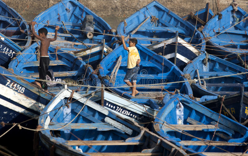 Boys stand amongst the many fishing boats in the port of Essouaira, Morocco. The present city of Essaouira was built during the 18th century by Mohammed III royalty free stock image