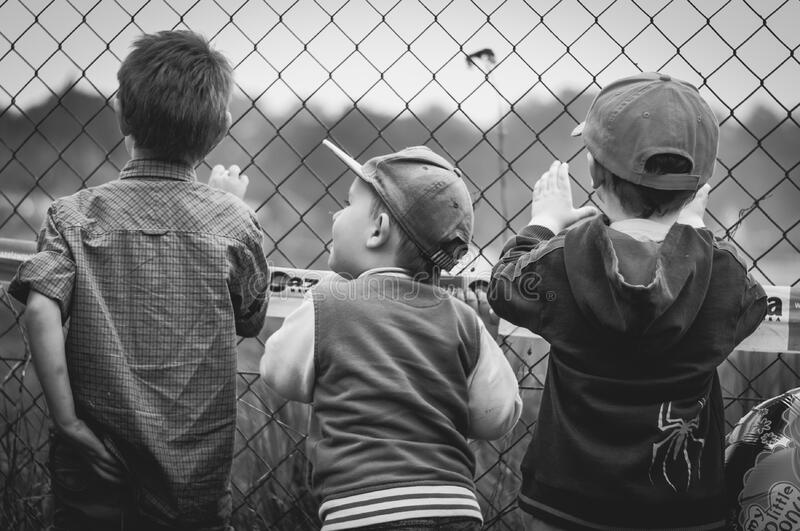 Boys standing by wire fence stock image