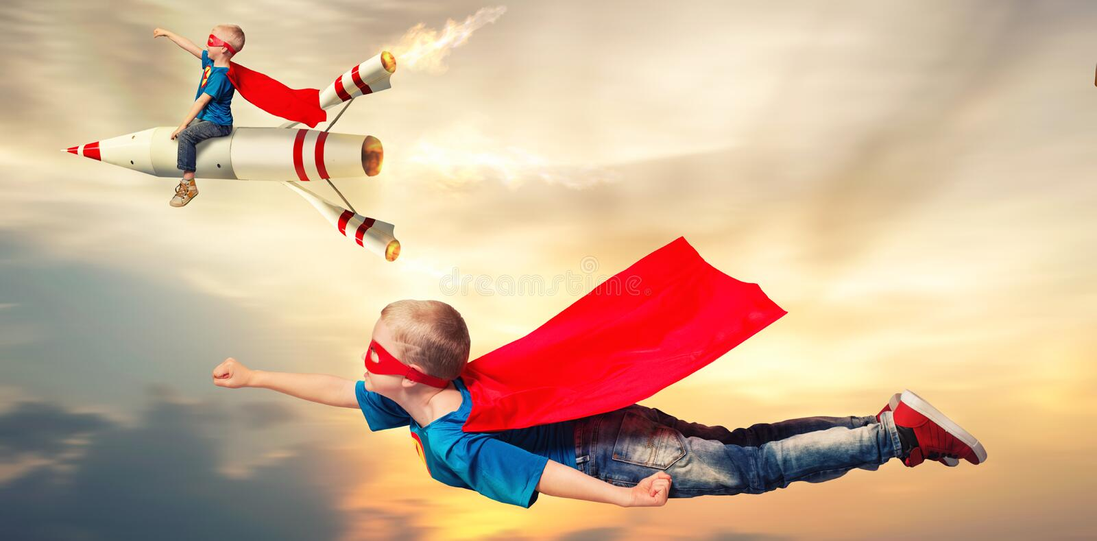 Children in superhero costumes fly and show super abilities. Boys in superhero costume guard the planet.Boys show super abilities stock photography