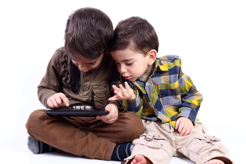 Boys with tablet. Boys playing game by tablet isolated on white stock photo