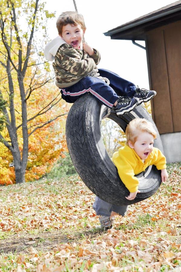 Boys tire swing fun royalty free stock photos
