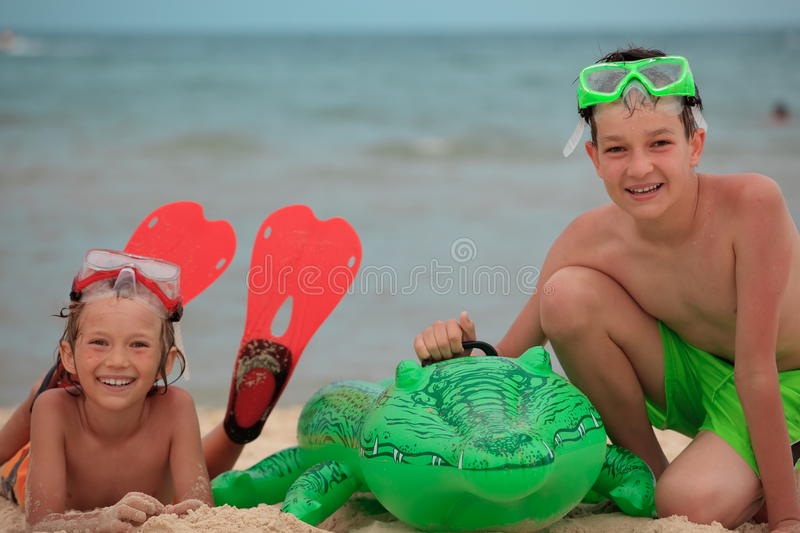 Boys with toy on beach. Two boys with a large green toy, playing in beach sand royalty free stock images