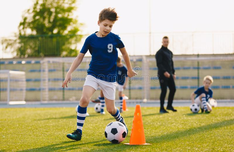 Boys training football dribbling in a field. Kids Running the Ball. Players develop soccer dribbling skills. Children training with balls and cones. Soccer royalty free stock photo