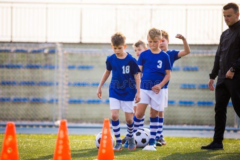 Boys Training Football on Pitch Witch Youth Coach Grupp för ungdomsskolans åldersgrupper vid utbildningsmöten med ungdomskollegie royaltyfri foto