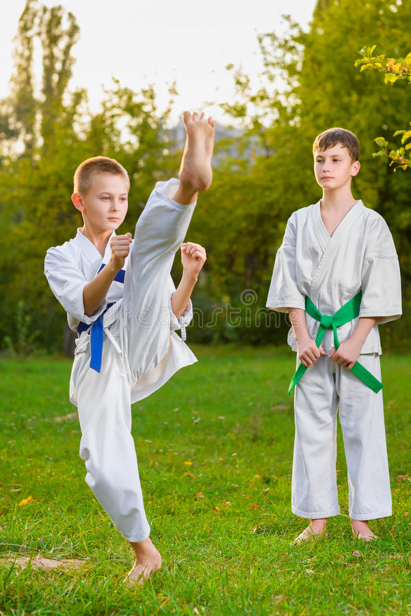 Boys in white kimono during training karate. Exercises at summer outdoors royalty free stock images