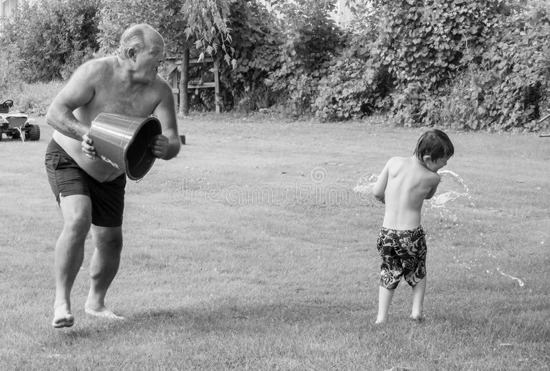 Boys will be boys. A grandfather splashing his grandson with water from a bucket on a hot summer day stock photography