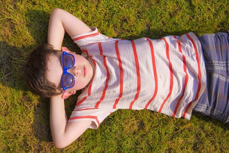 Boywith okulary przeciwsłoneczni sunbathing na trawie w lecie fotografia stock