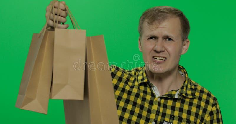 Boze agressieve mens met het winkelen zakken het schreeuwen Twee in: 1 royalty-vrije stock afbeeldingen