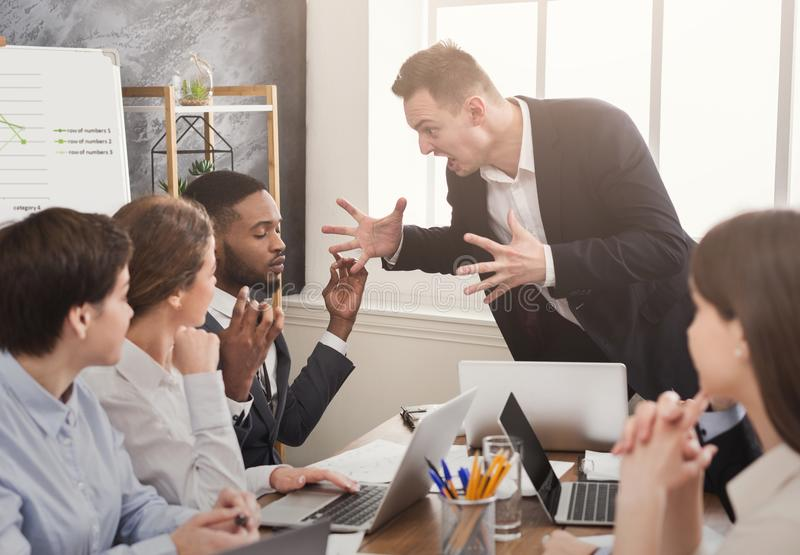 Boze bedrijfsmens die bij werknemer in bureau gillen stock foto