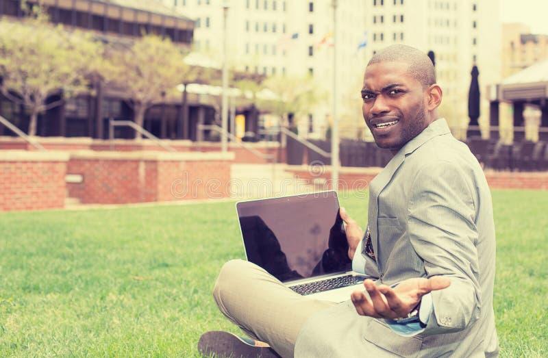 Boze bedrijfsmens met laptop zittings in openlucht collectief bureau stock fotografie