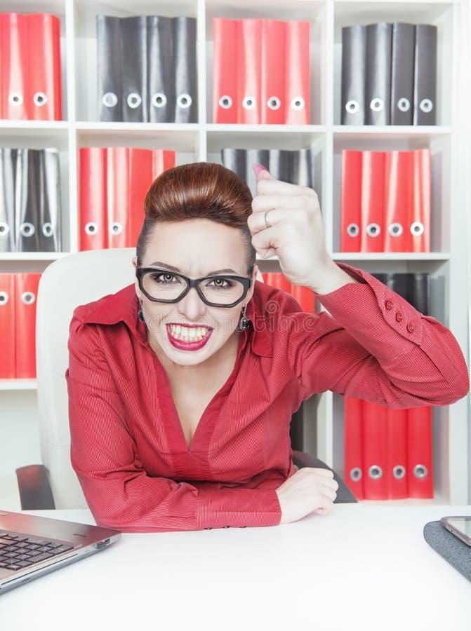 Boze bedrijfsvrouw die grote vuist in bureau schudt stock afbeelding