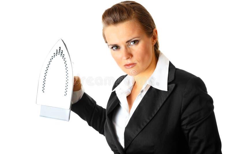 Boze bedrijfsvrouw die menacingly ijzer houdt stock afbeeldingen