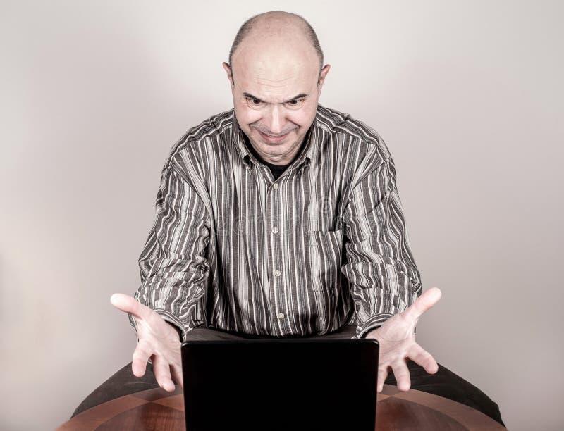 Boze en zenuwachtige zakenman met laptop stock fotografie
