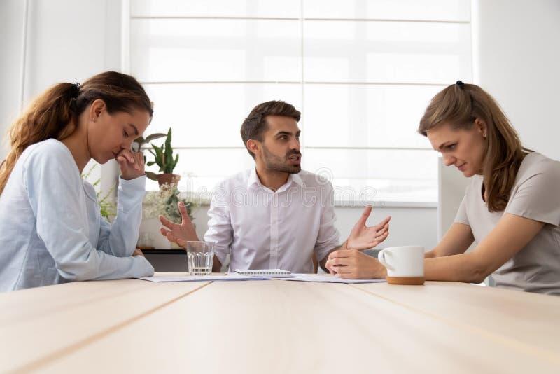 Boze gemiddelde mannelijke werkgever die kritiserend beklemtoonde droevige vrouwelijke werknemers schreeuwen stock foto's