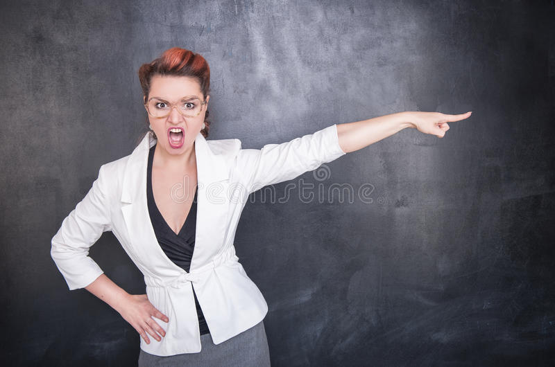 Boze gillende leraar die bord op achtergrond wijzen stock foto's