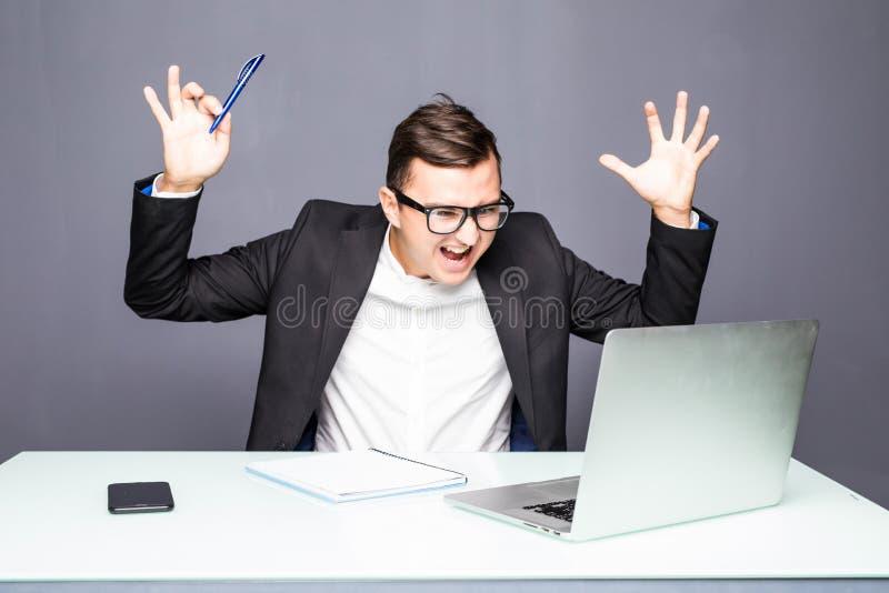 Boze hogere zakenmanzitting bij zijn bureau en het gillen Boze zakenman met teveel werk in bureau Beklemtoond knap youn royalty-vrije stock foto