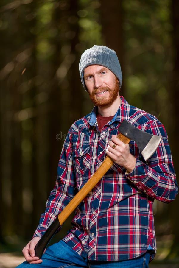 Boze houtvester met een grijns met een bijl in zijn handen stock fotografie