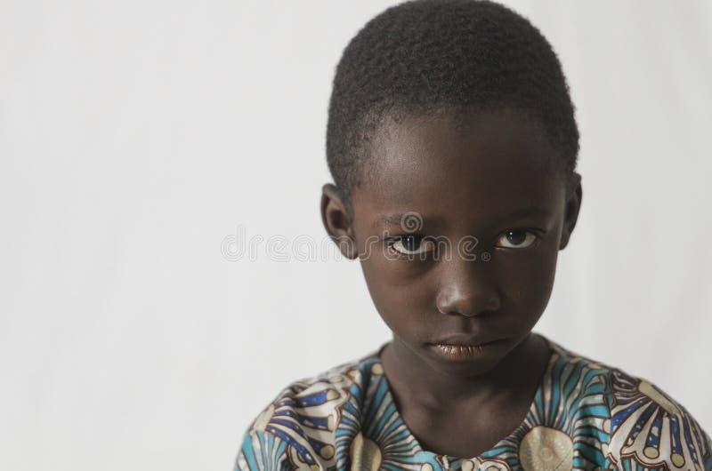 Boze jonge Afrikaanse jongen die op wit wordt geïsoleerd, die zijn gezicht tonen voor stock fotografie