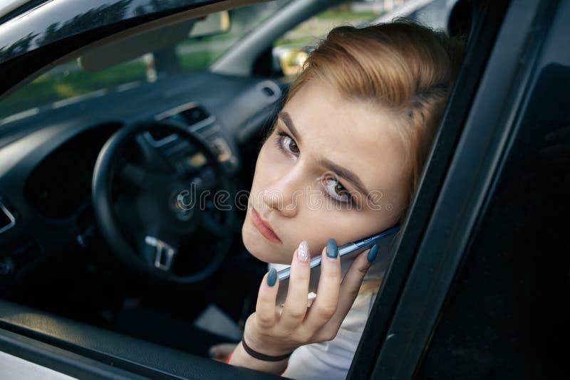 Boze jonge vrouw in auto stock foto
